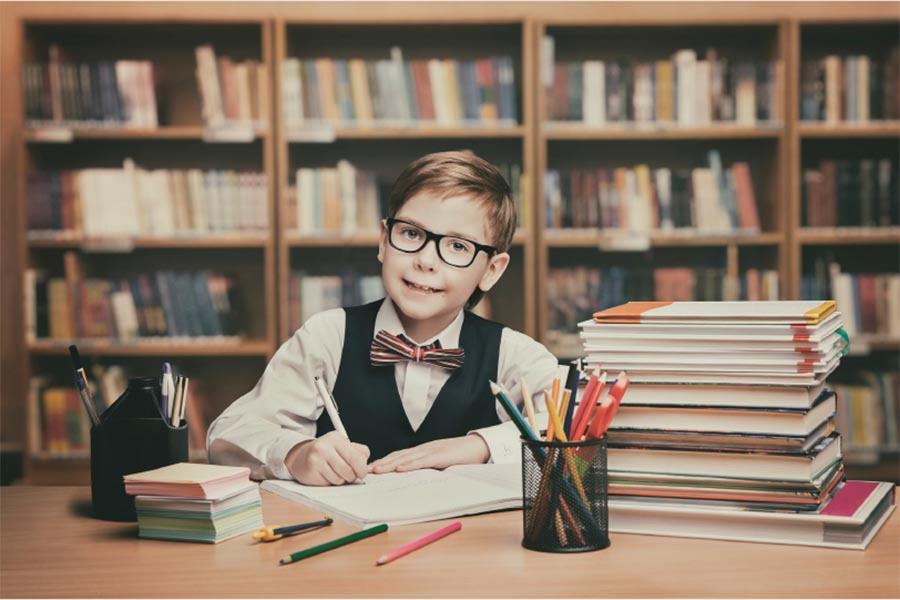 young boy at a library writing desk